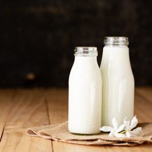 Fresh milk two bottle glass on the wooden table Black background